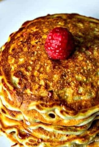 stack of raspberry pancakes on a white plate