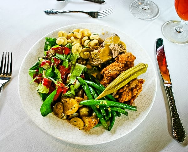 A dinner plate with okra, chicken, and vegetables