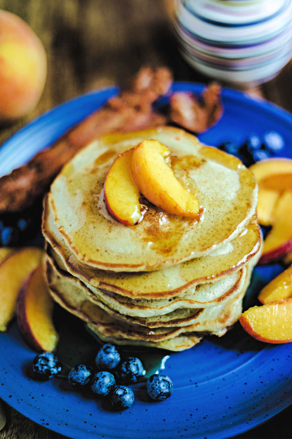 a stack of pancakes on a blue cake with peaches and blueberries scattered around and syrup drizzled on top.