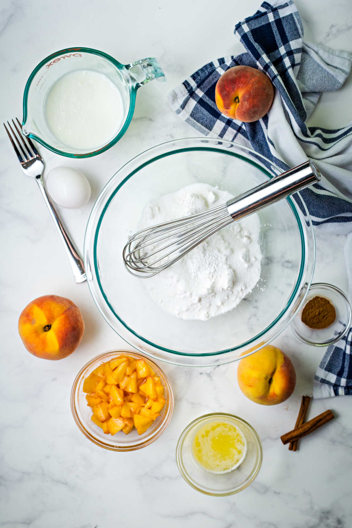 ingredients for peach pancakes on a kitchen counter: flour, diced peaches, melted butter, egg, and buttermilk.