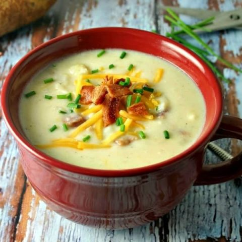 A bowl of soup on a table, with Baked potato soup