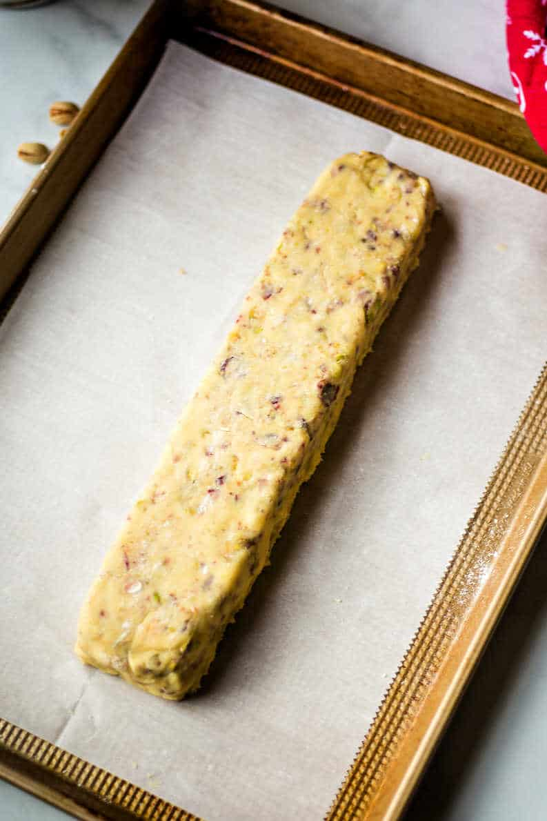 unbaked log of biscotti on a parchment paper lined baking sheet