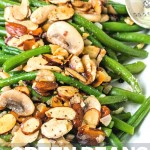 Green beans almondine on a white platter topped with almonds and mushrooms.