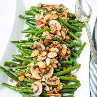green bean almondine on a white serving platter with a silver serving spoon and with almonds and mushrooms scattered on top.