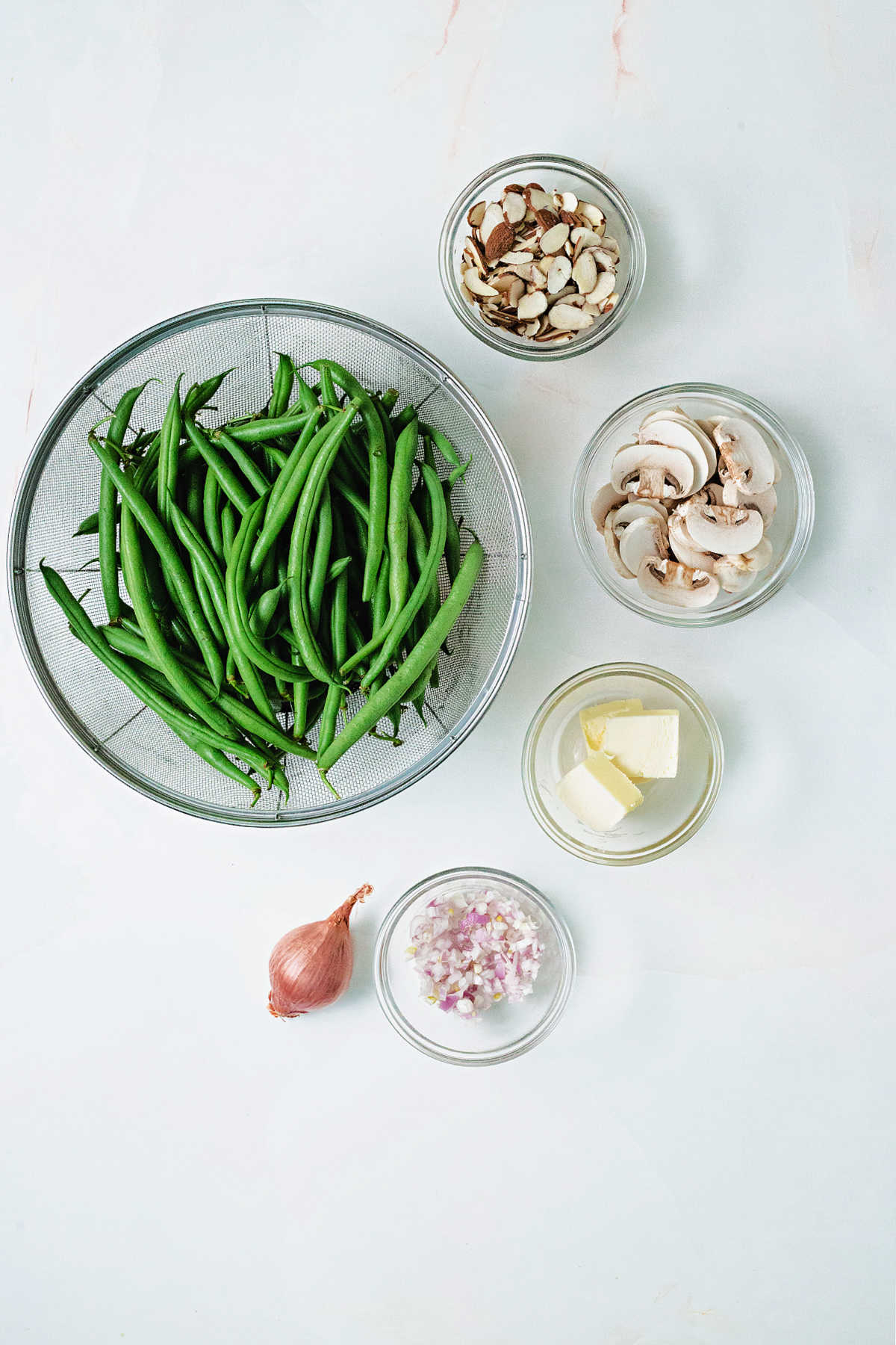 ingredients for green beans almondine on a counter: fresh green beans, butter, shallots, sliced almonds, mushrooms.