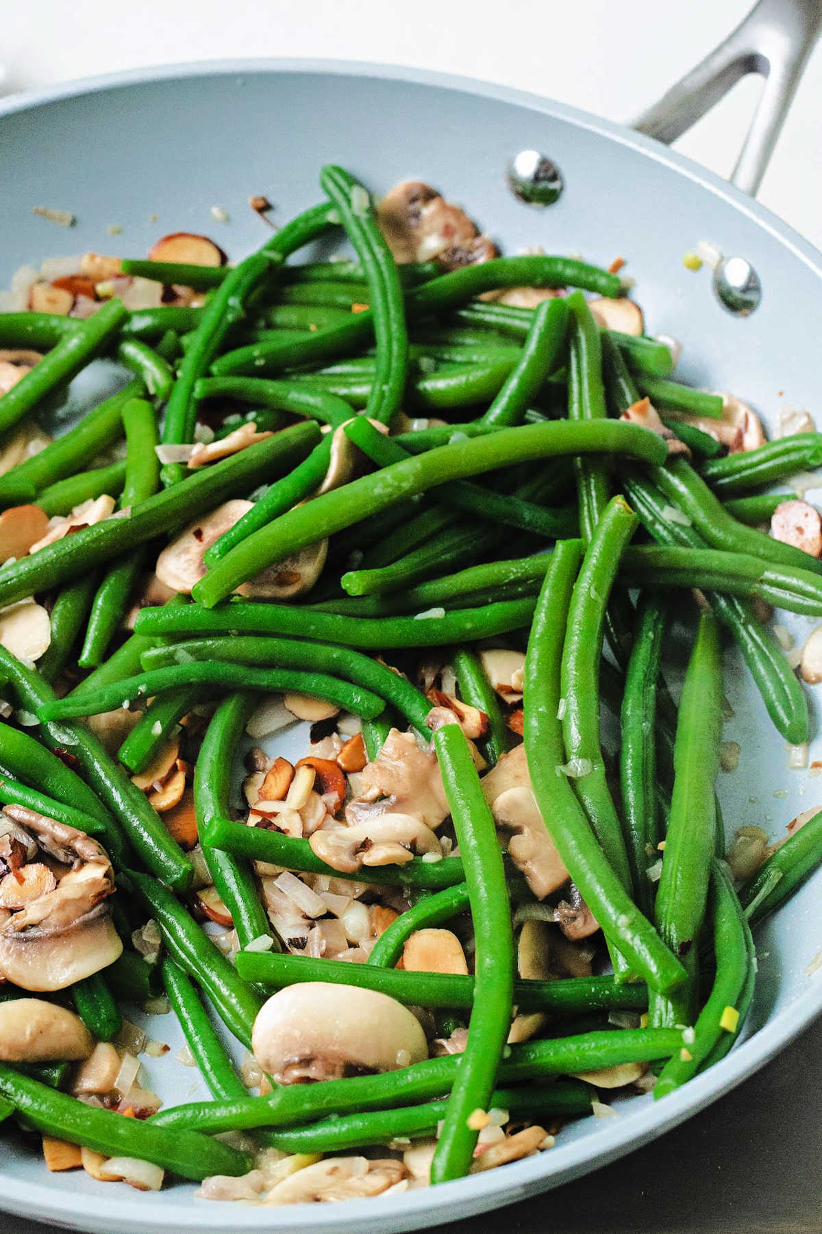 close up shot of green beans cooking in a frying pan with almonds and mushrooms.