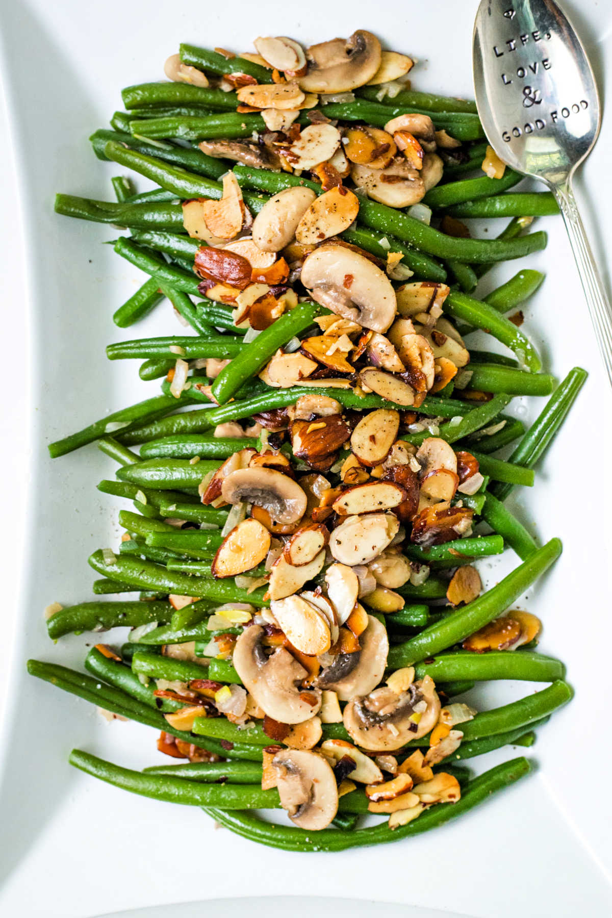green bean almondine on a white serving platter with almonds and mushrooms scattered on top.