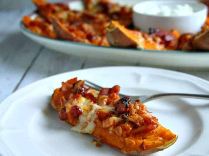 A plate of food with a piece of loaded sweet potato skins