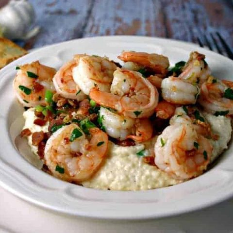 A plate of Smokey Shrimp and Grits on a table