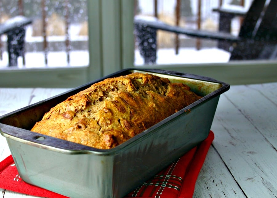 A load pan sitting on top of a wooden table, with Whole Wheat Honey Banana Bread