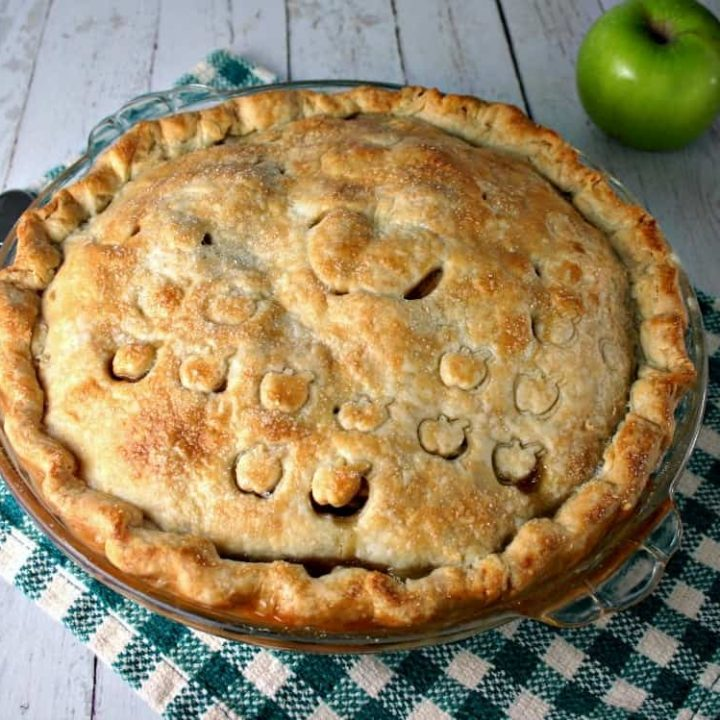 An apple pie sitting on top of a wooden table