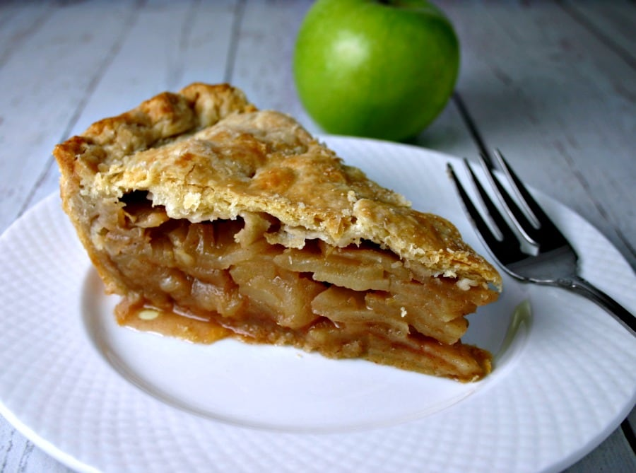 A slice of pie on a plate, with Mom\'s Apple pie