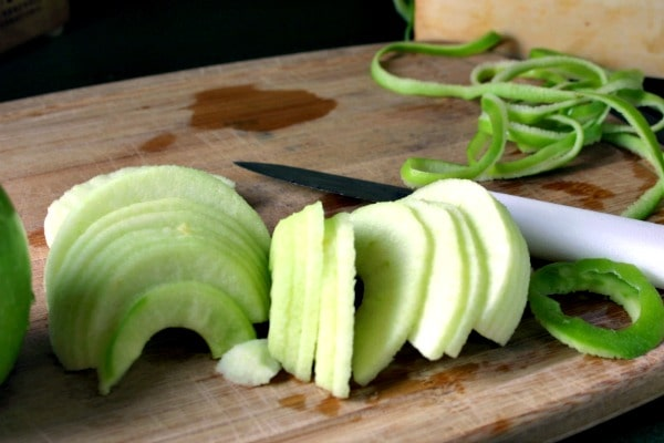 A apple slices sitting on top of a wooden cutting board, with Mom\'s Apple Pie