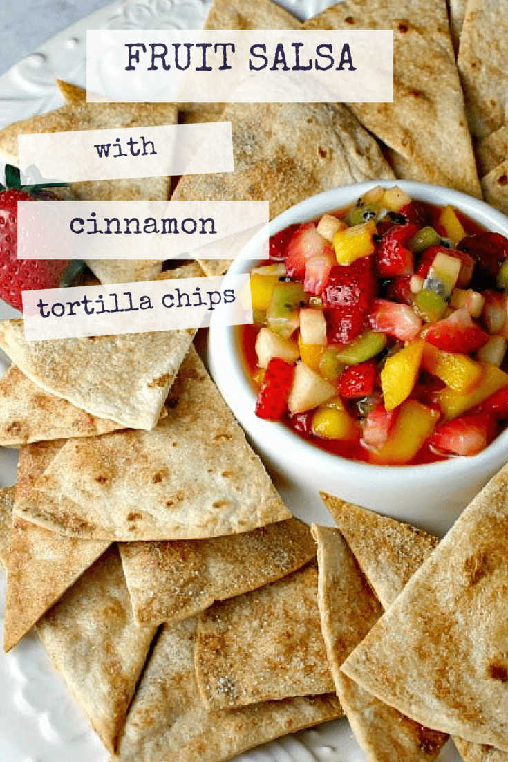 A bowl of fruit salsa with toasted pita chips on a platter.