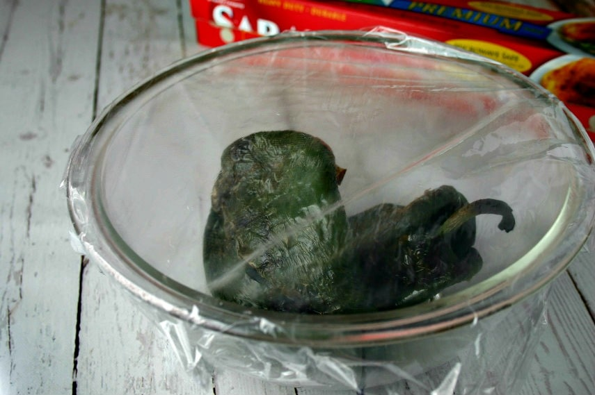 A bowl of grilled poblano peppers covered with plastic wrap