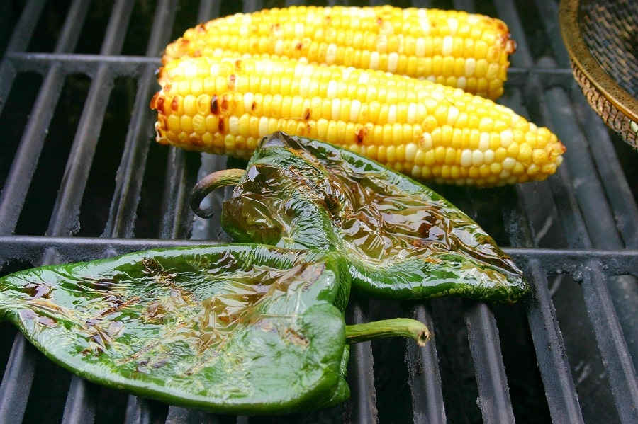 A close up of corn on the cob and poblano peppers on a gas grill