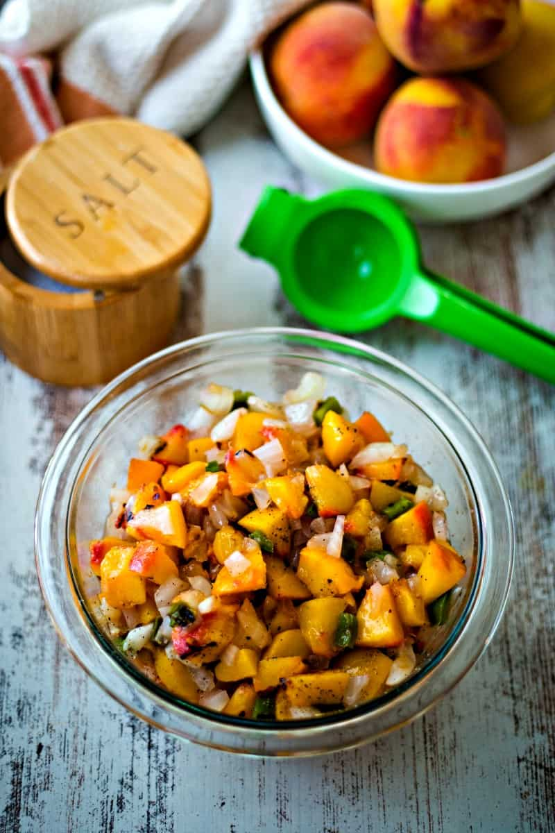 a bowl of peaches on counter with a bowl of peach salsa