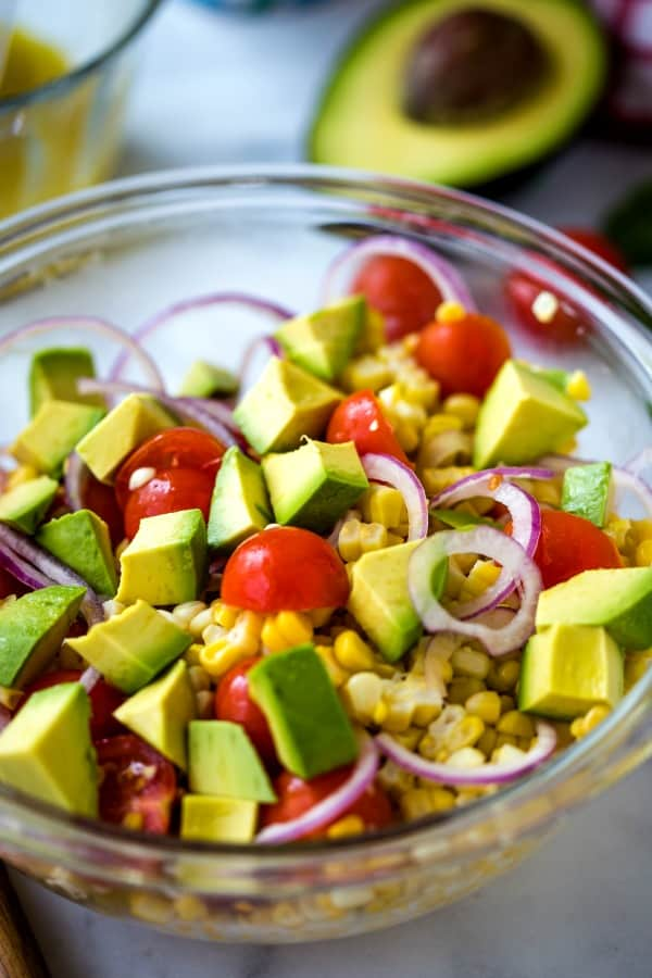 avocado, fresh corn, tomato, and red onion in a glass bowl