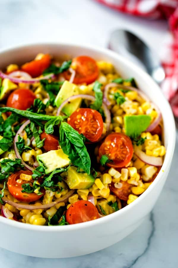 corn, tomatoes, and avocado salad in a white bowl