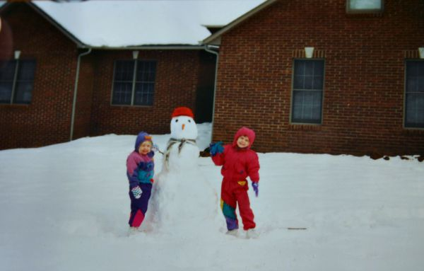 two little girls building a snowman in from of a brick house