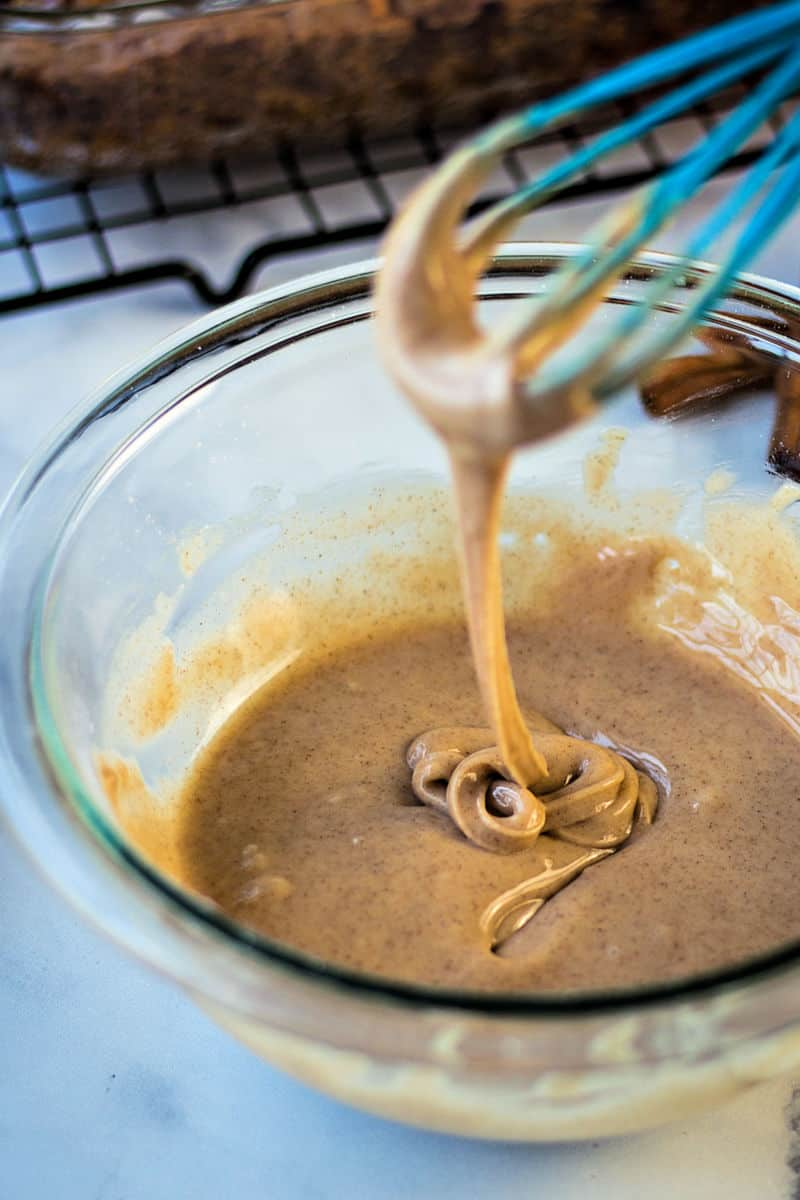 a whisk swirling cinnamon glaze in a glass bowl