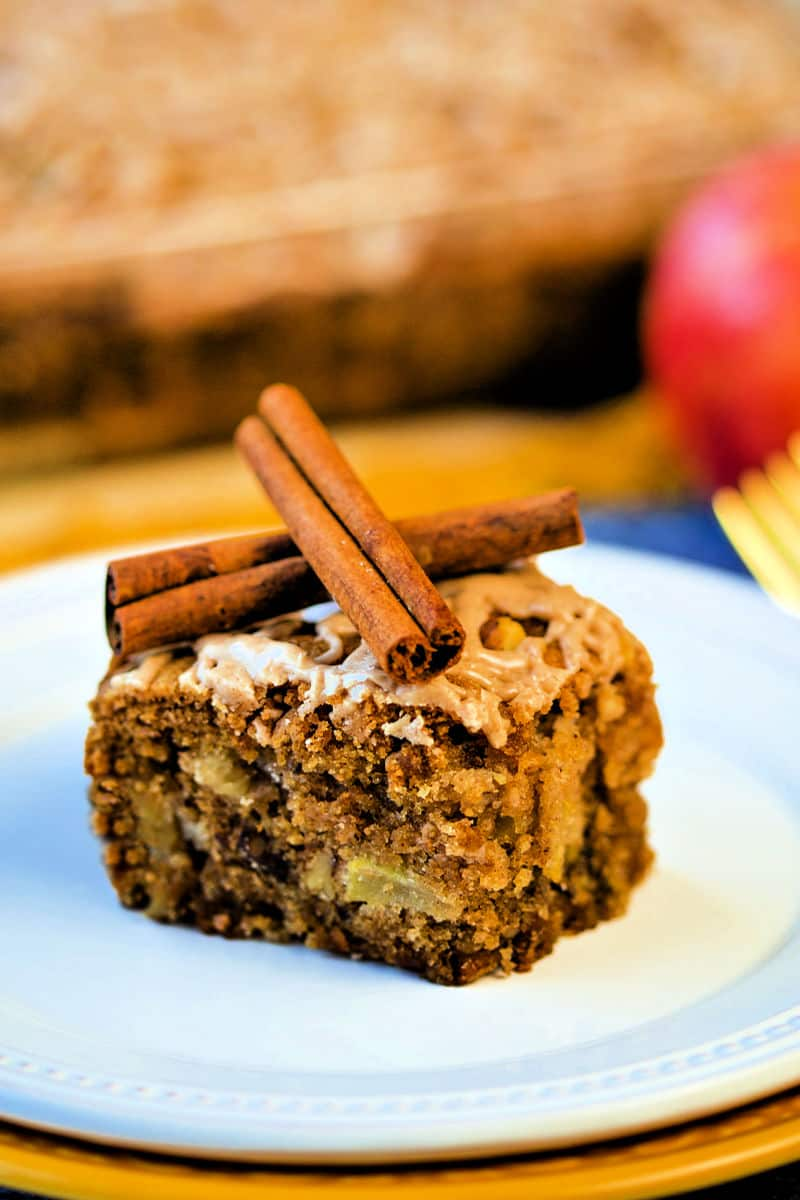 slice of apple cake with cinnamon stick criss-crossed on top as garnish on a white plate