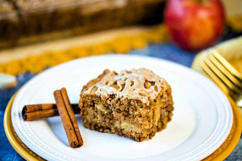 a slice of apple cake with cinnamon sticks on a white plae with a gold fork and napkin