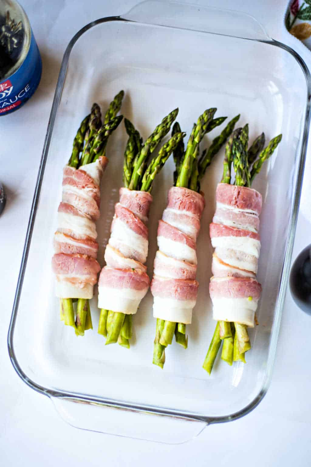 asparagus wrapped in raw bacon in a baking dish