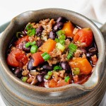a soup mug filled with black bean and sweet potato chili sitting on a white plate.