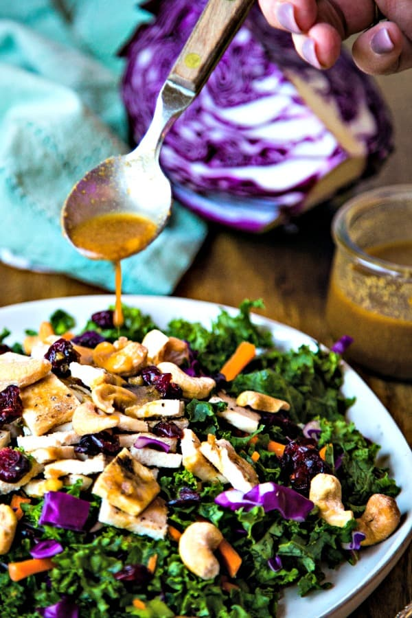 a spoon drizzling vinaigrette over a plate of Chopped Chicken Kale Salad