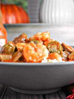 A bowl of food on a table, with Chicken, Sausage, and Shrimp Gumbo