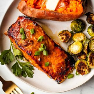 grilled salmon with brussel sprouts and a baked sweet potato on a white plate