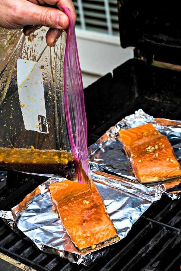Cooking salmon filets on the grill in aluminum foil boats with marinade