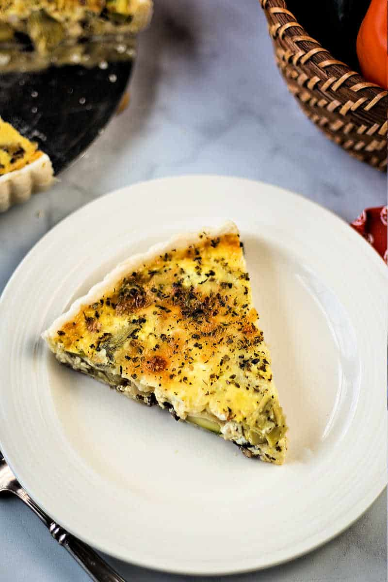 A sesrving of California Quiche baked with zucchini, peppers, onions, mushrooms, and artichoke hearts on a white plate on breakfast table