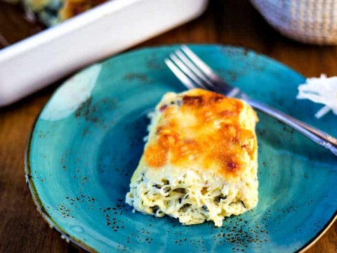 A serving of spinach spaghetti squash casserole on a blue plate with a fork