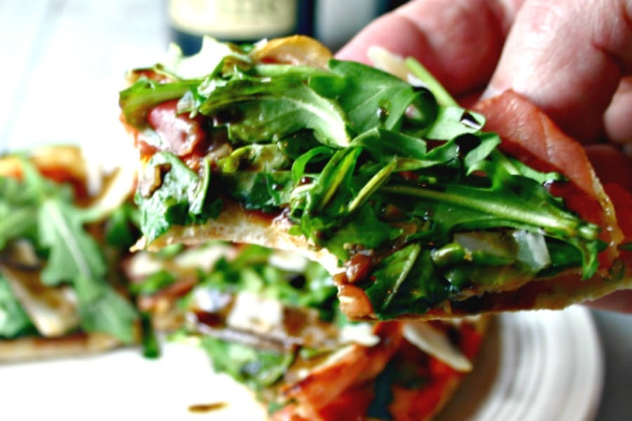 Close up of a piece of Arugula Prosciutto Personal Pita Pizza