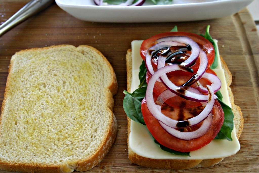 Two slices of bread on a cutting board, with basil, red onions, and tomato slices for Bruschetta Waffle Panini