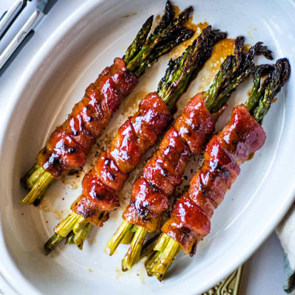 bacon wrapped asparagus bundles in a white baking dish