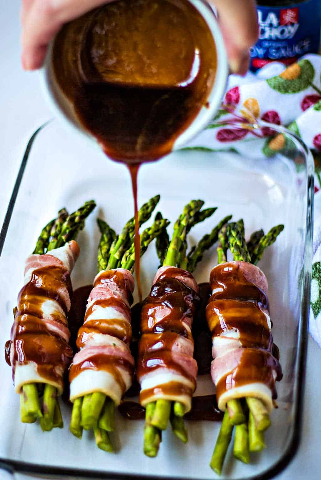 pouring brown sugar soy sauce over bacon wrapped asparagus in a baking dish