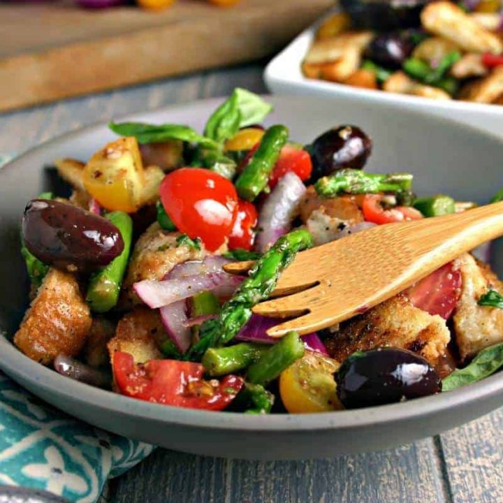 A bowl of Grilled Asparagus Panzanella Salad on a table