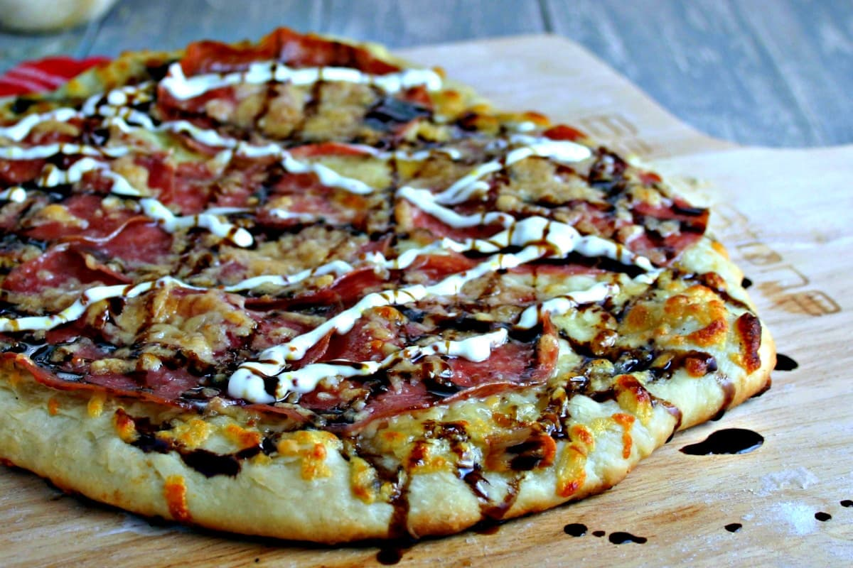 A pizza sitting on top of a wooden cutting board, with Salami Pizza with Garlic Dijon Aioli