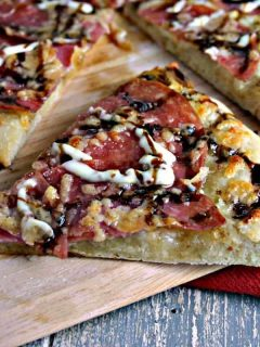 A slice of pizza sitting on top of a wooden cutting board, with Salami Pizza with Garlic Dijon Aioli