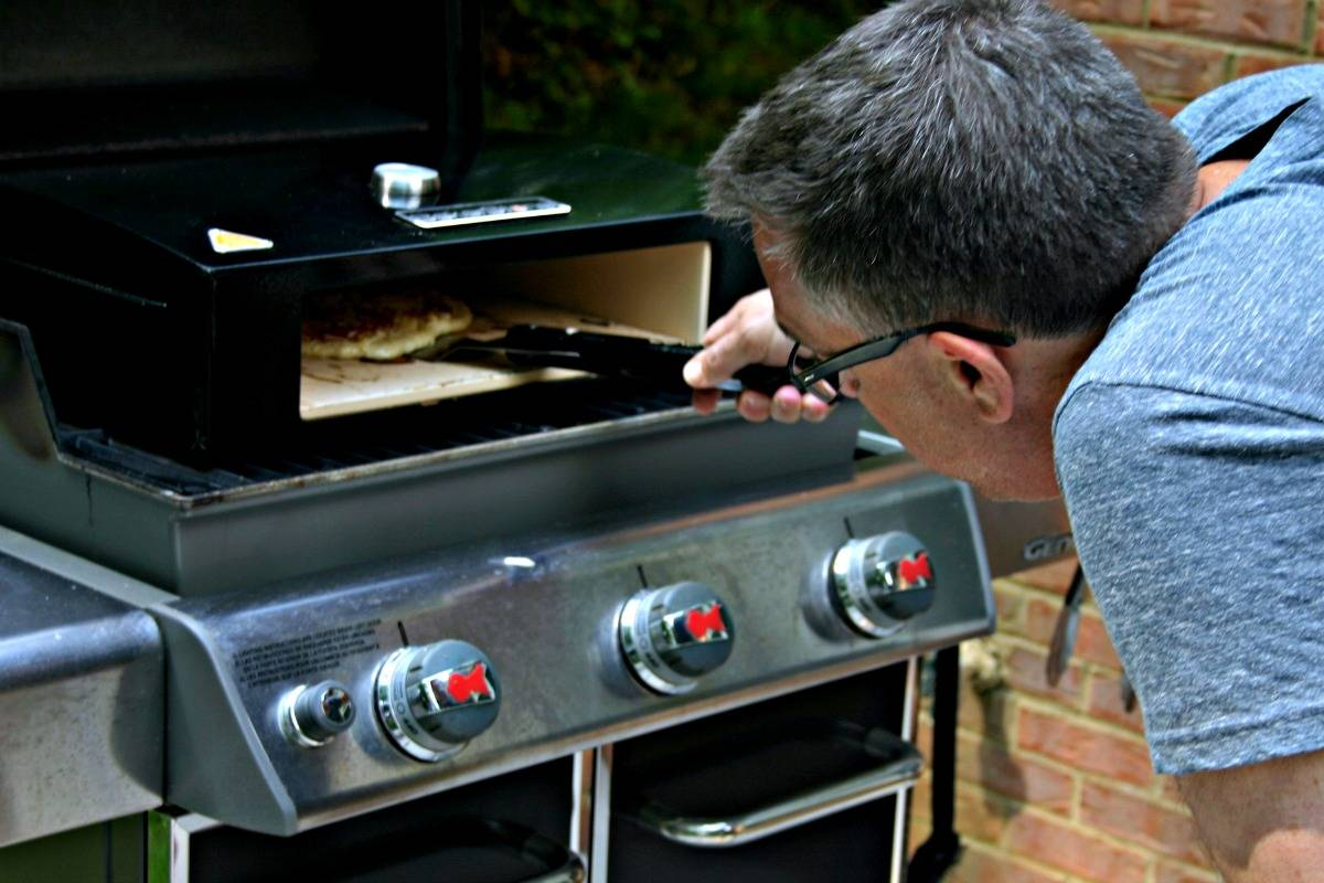 A man sliding a pizza into a grill-top pizza oven