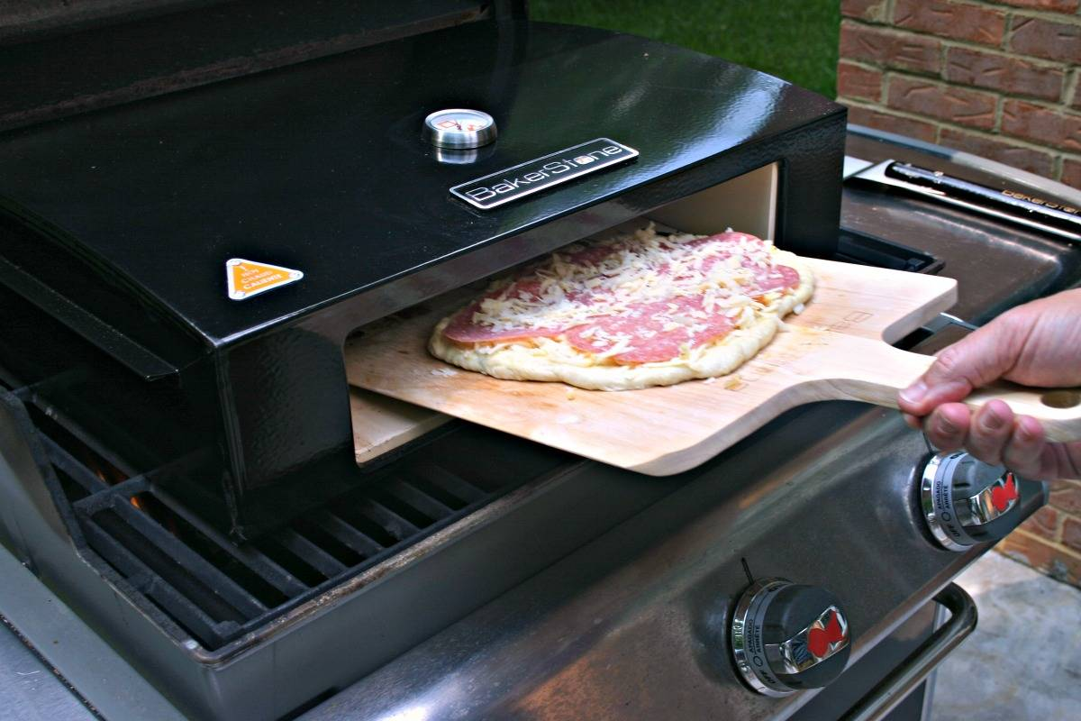 Sliding a pizza into a grill-top pizza oven