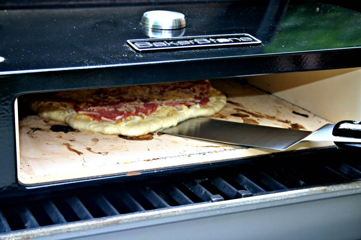 A pizza sitting in a grill top pizza oven