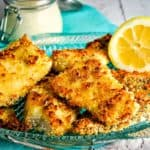 Crispy oven-fried fish with lemon on fish platter
