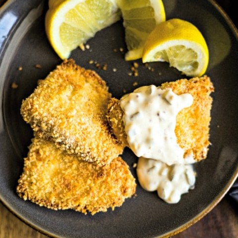 three fish filets with tartar sauce and lemon wedges on a slate plate
