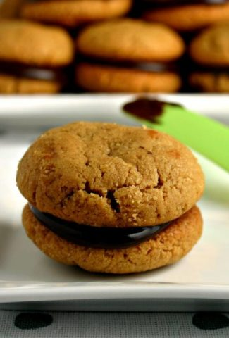 A flourless peanut butter cookie with chocolate filling on a plate