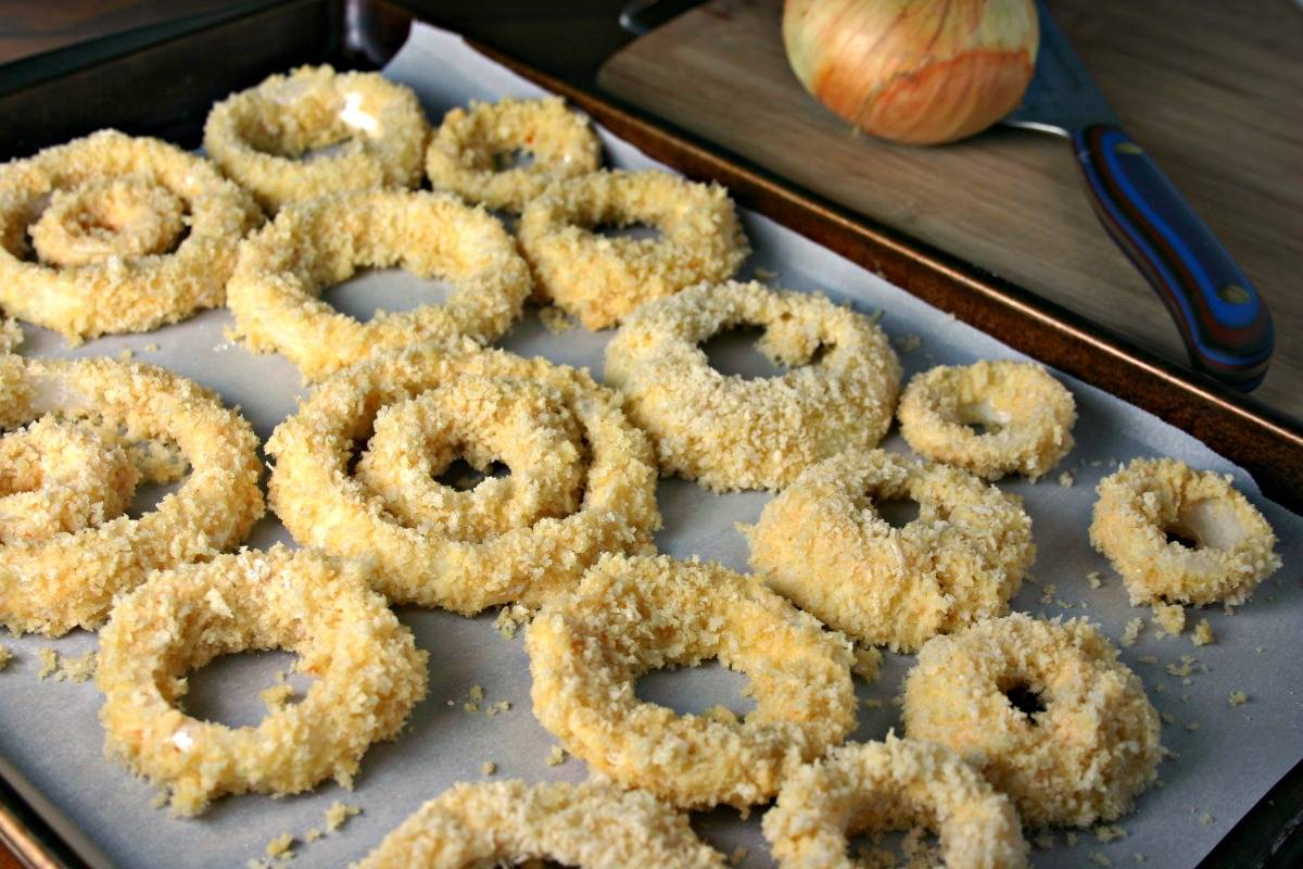 A close up of food on a baking sheet, with Crispy Oven Baked Onion Rings