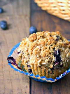 A muffin sitting on top of a wooden table, with Blueberry Oatmeal Muffins